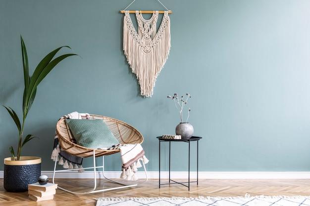 Стильная композиция креативного и уютного интерьера гостиной с журнальным столиком, креслом из ротанга, растениями, ковром и аксессуарами .boho. стены и паркет из эвкалипта.