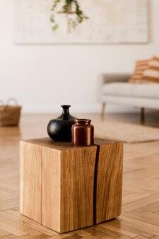 커피 테이블, 식물, 카펫 및 아름다운 액세서리를 갖춘 독창적인 아파트 인테리어의 세련된 구성. 흰색 벽과 쪽모이 세공 마루 바닥.