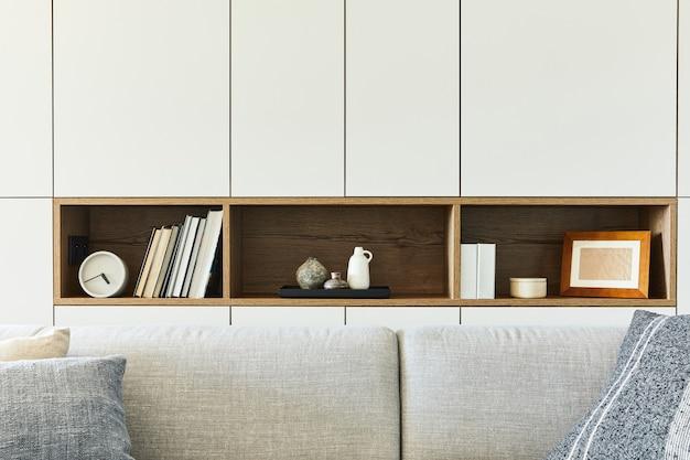 책, 시계 및 기타 개인 액세서리와 같은 창의적인 거실 인테리어 세부 사항의 세련된 구성. 화이트 패널. 세부. 주형.