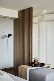 커피 테이블, 푸프, 램프 및 기타 개인 액세서리와 같은 창의적인 거실 인테리어 세부 사항의 세련된 구성. 나무 패널. 세부. 주형.