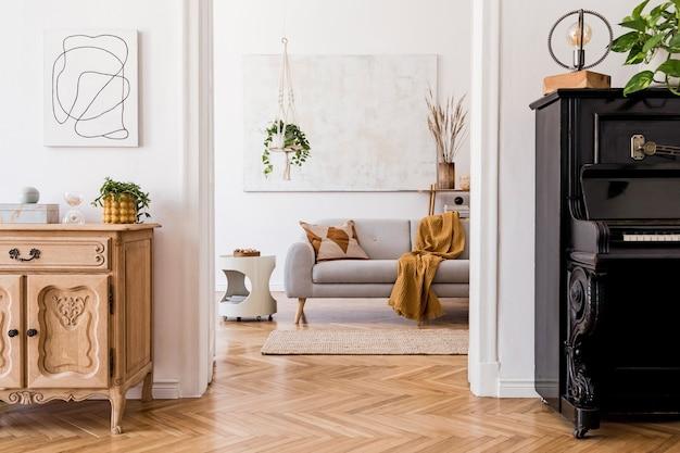 灰色のソファ、コーヒーテーブル、植物、カーペット、美しいアクセサリーを備えたクリエイティブで広々としたアパートメントインテリアのスタイリッシュな構成。白い壁と寄木細工の床。
