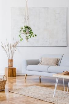 회색 소파, 커피 테이블, 식물, 카펫 및 아름다운 액세서리를 갖춘 독창적인 넓은 아파트 인테리어의 세련된 구성. 흰색 벽과 쪽모이 세공 마루 바닥.