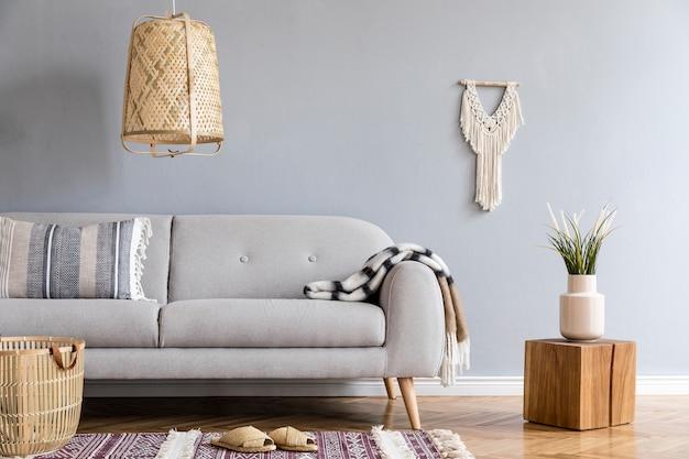 Стильная композиция креативного интерьера просторной гостиной с копией пространства, диваном, журнальным столиком, растениями, ковром и аксессуарами. серые стены и паркетный пол. стиль бохо. шаблон
