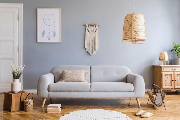 프레임, 소파, 커피 테이블, 식물, 카펫 및 액세서리가있는 창의적인 넓은 거실 인테리어의 세련된 구성. 회색 벽과 쪽모이 세공 마루 바닥.