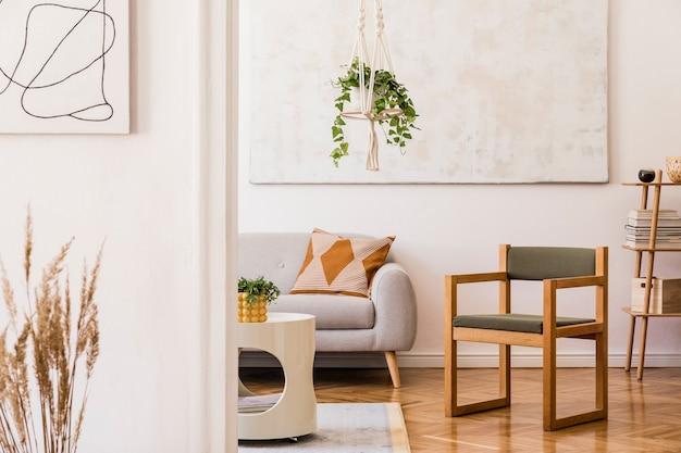 Стильная композиция креативного интерьера просторной гостиной с серым диваном, креслом, растениями, ковром, картинами и аксессуарами.