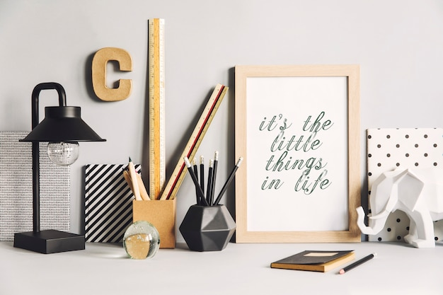 モックアップポスターフレーム、ランプ、ノートブック、象、アクセサリーを備えたクリエイティブなワークスペースのスタイリッシュな構成。中立的な壁。グレー、黒、白のミニマルなコンセプト。
