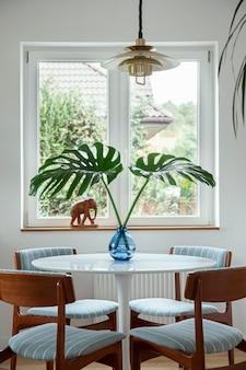 디자인 테이블, 의자, 꽃병에 열대 잎, 창문 및 가정 장식의 우아한 장식이있는 식당 인테리어의 세련된 구성. 주형.
