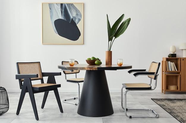 Стильная композиция интерьера столовой с дизайнерским столом, современными стульями, декором, тропическим листом в вазе, фруктами, книжным шкафом, абстрактными картинами и элегантными аксессуарами в домашнем декоре.