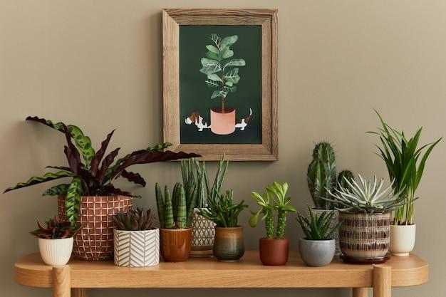 モックアップポスターフレームを備えたホームガーデンインテリアのスタイリッシュな構成は、さまざまなデザインの鉢にたくさんの美しい植物、サボテン、多肉植物、空気植物を満たしました。家の園芸の概念。テンプレート。