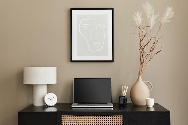 Стильная композиция интерьера домашнего офиса с черным деревянным столом, стулом, сушеным цветком в вазе, ноутбуком, рамкой, дизайнерской настольной лампой, часами и элегантными офисными принадлежностями.