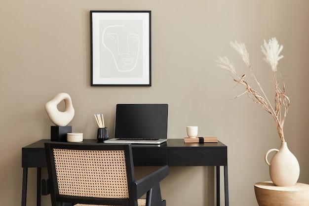 Стильная композиция интерьера домашнего офиса с черным деревянным столом, стулом, сушеным цветком в вазе, ноутбуком, макетом рамки для плаката, чашкой кофе, часами и элегантными офисными аксессуарами. шаблон.