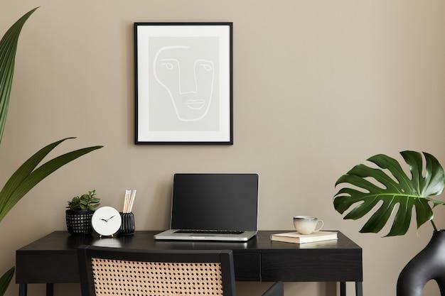 검은 나무 책상, 의자, 꽃병에 열대 꽃, 노트북, 프레임, 커피 한잔, 시계 및 우아한 사무실 액세서리와 함께 홈 오피스 인테리어의 세련된 구성 ..