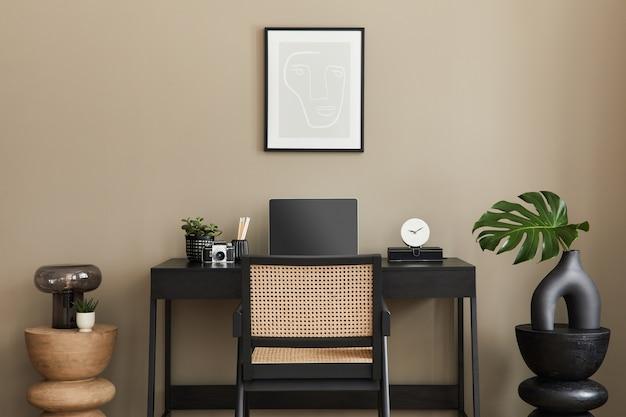 Стильная композиция интерьера домашнего офиса с черным деревянным столом, стулом, тропическим цветком в вазе, ноутбуком, макетом рамки для плаката, чашкой кофе, часами и элегантными офисными аксессуарами
