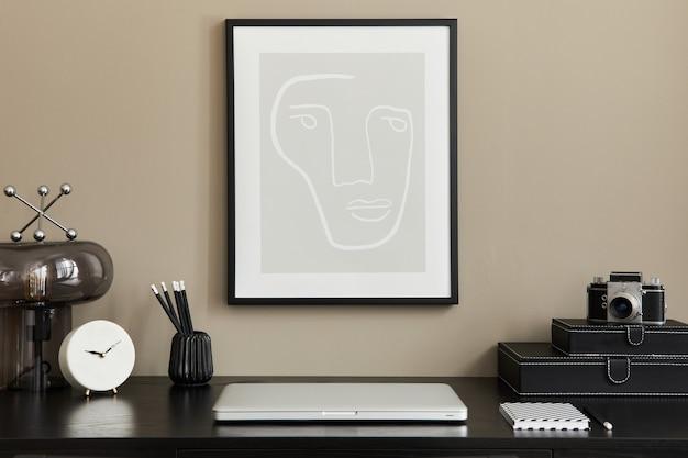 검은 나무 책상, 노트북, 프레임, 디자인 테이블 램프, 사진 카메라, 주최자, 시계 및 우아한 사무실 액세서리와 함께 홈 오피스 인테리어의 세련된 구성 ..