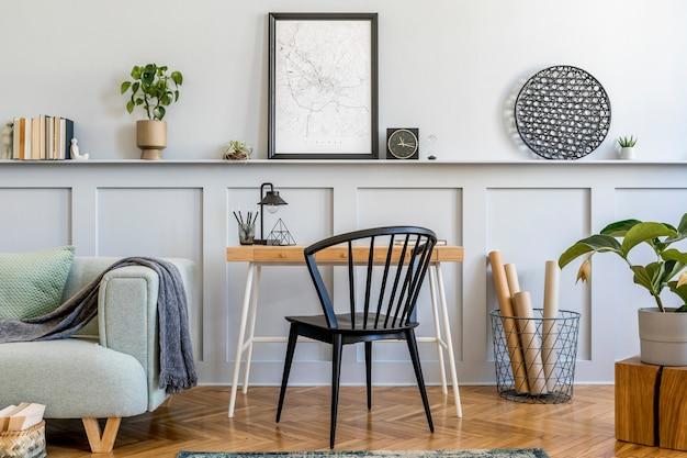 Стильная композиция домашнего офиса с диваном, деревянным столом, дизайнерским креслом, рамкой для макета плаката, ковром, растениями, книгами, лампой, канцелярскими принадлежностями и личными аксессуарами в современном домашнем декоре.