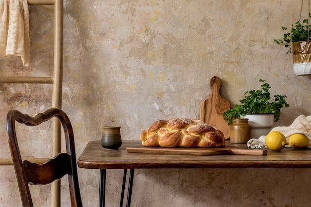 Стильная композиция кухонного интерьера с семейным столом, овощами, чайником, десертом, продуктами питания, растениями и кухонными принадлежностями в концепции домашнего декора ваби-саби.