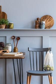 가정 장식의 회색 개념에 나무 패밀리 테이블, 의자, 야채, 허브, 식물, 과일, 식품 공급 및 주방 액세서리와 주방 인테리어의 세련된 구성.
