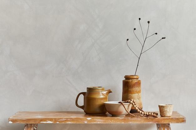 コピースペース、レトロなスタイルのベンチ、粘土の花瓶と食器を備えたリビングルームのインテリアのスタイリッシュな構成。素朴なインスピレーション。夏の雰囲気。ベージュの壁。レンプレート。