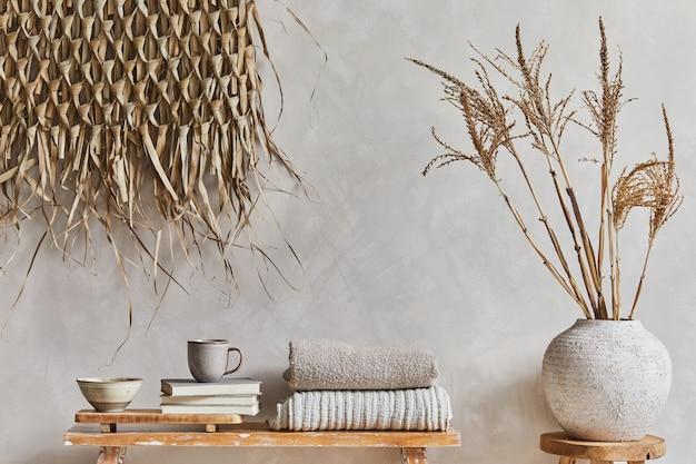 コピースペース、レトロなスタイルのベンチ、粘土の花瓶、食器棚、わらの壁の装飾が施されたリビングルームのインテリアのスタイリッシュな構成。素朴なインスピレーション。夏の雰囲気。ベージュの壁。レンプレート。