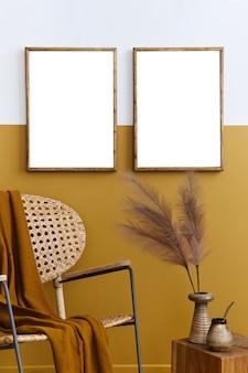 세련된 디자인의 등나무 안락의자, 2개의 모의 포스터 프레임, 식물, 큐브, 팰리드 및 개인용 액세서리가 있는 세련된 구성의 꿀 노란색 홈 장식. 주형.
