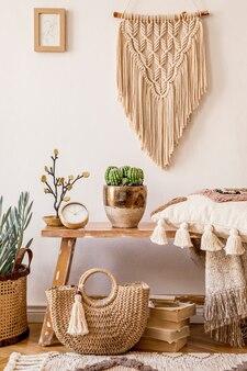 현대 가정 장식의 프레임, 나무 벤치, 베개, 격자 무늬, 여성 가방, 책, 선인장, 마크라메, 식물, decortaion 및 우아한 개인 액세서리가있는 거실 인테리어의 세련된 구성.