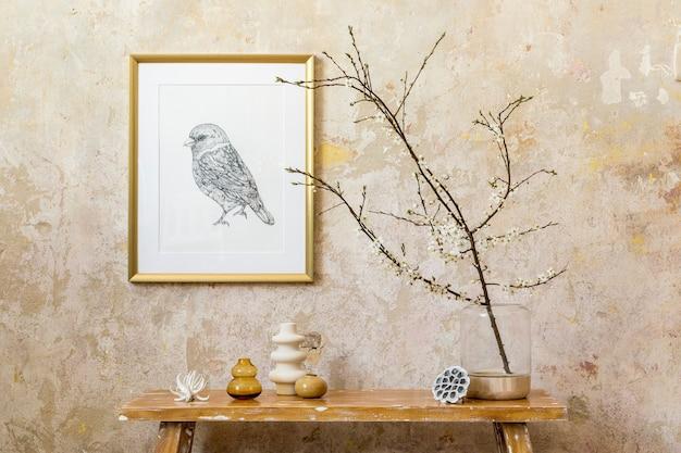Стильная композиция интерьера гостиной с золотой рамкой, деревянной скамейкой, декором, сушеным цветком в вазе и элегантными личными аксессуарами в современном домашнем декоре.