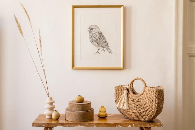 Стильная композиция интерьера гостиной с золотой рамкой, деревянной скамейкой, золотыми часами, шкатулками, сухоцветами в вазе, женской сумкой и элегантными личными аксессуарами в современном домашнем декоре.