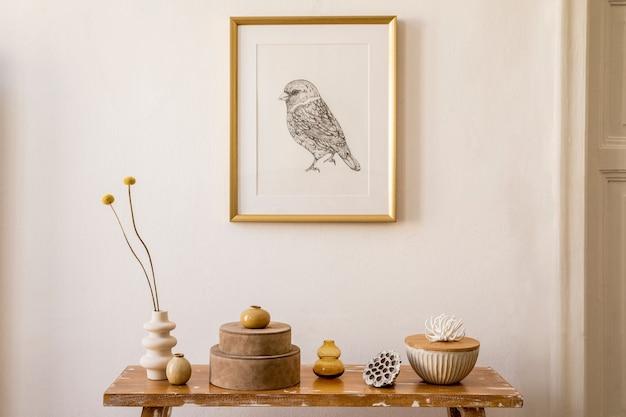 ゴールドのモックアップフレーム、木製のベンチ、ボックス、花瓶のドライフラワー、モダンな家の装飾のエレガントなパーソナルアクセサリーを備えたスタイリッシュなリビングルームのインテリア。
