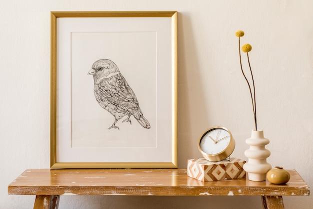 Стильная композиция интерьера гостиной с золотой рамкой-макетом, деревянной скамейкой, золотыми часами, коробкой, сухоцветами в вазе, женской сумкой и элегантными личными аксессуарами в современном домашнем декоре.