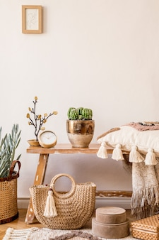 モックアップフレーム、木製のベンチ、枕、格子縞、籐のバスケット、植物、装飾、コピースペース、モダンな家の装飾のエレガントなパーソナルアクセサリーを備えたリビングルームのインテリアのスタイリッシュな構成。