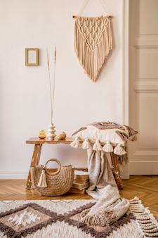 Стильная композиция интерьера гостиной с макетом каркаса, деревянной скамейкой, подушкой, пледом, женской сумкой, книгами, кактусами, макраме, растением, декором и элегантными личными аксессуарами в современном домашнем декоре.