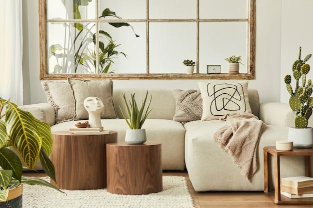 デザインベージュのソファ、木製のスツール、サボテン、植物、本、装飾、家具、エレガントなパーソナルアクセサリーを備えたリビングルームのスタイリッシュな構成。モダンな家の装飾。オープンスペース。レンプレート。