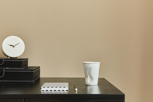 Стильная композиция офисного интерьера с черным столом, чашкой кофе, нотами, дизайнерскими белыми часами и настольным органайзером. шаблон. бежевая стена. скопируйте пространство.