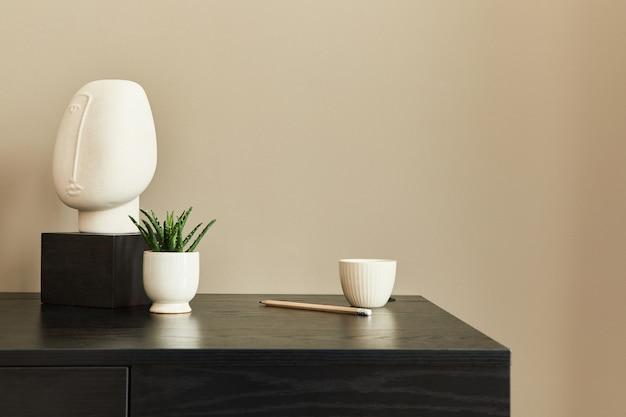 Стильная композиция офисного интерьера с черным письменным столом, дизайнерской скульптурой, планшетом, блокнотом и письменным органайзером. шаблон. бежевая стена. скопируйте пространство.
