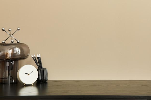 Стильная композиция офисного интерьера с черным столом, дизайнерской настольной лампой, белыми часами и настольным органайзером. бежевая стена. скопируйте пространство.