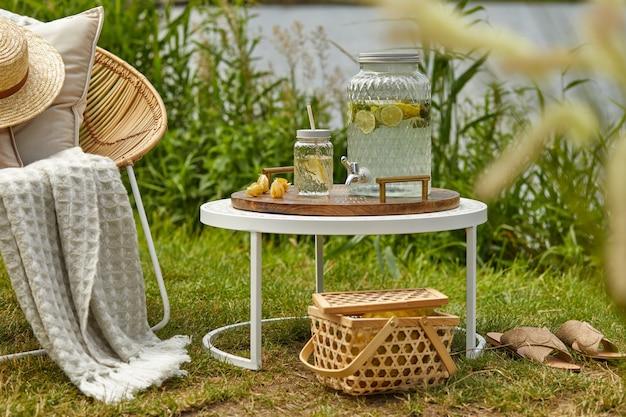デザインの籐のアームチェア、コーヒーテーブル、格子縞、枕、飲み物、エレガントなアクセサリーを備えた湖の屋外ガーデンのスタイリッシュな構成。夏のチルアウトムード。