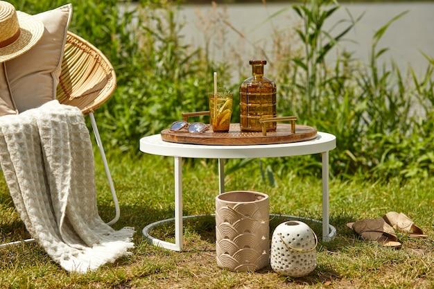 디자인 등나무 안락 의자, 커피 테이블, 격자 무늬, 베개, 음료 및 우아한 액세서리와 함께 호수에 야외 정원의 세련된 구성.