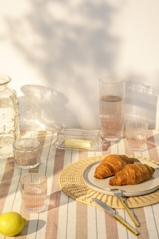 木製のテーブル、食べ物、飲み物、キッチンアクセサリー、ベージュのテーブルクロス、夏の木陰のある屋外キッチンスペースのスタイリッシュな構成。田舎の気分。テンプレート。