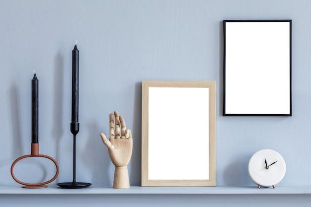 두 개의 모의 포스터 프레임과 검은 양초가 있는 실내 디자인의 세련된 구성