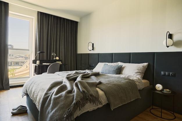 小さなモダンなベッドルームのインテリアのスタイリッシュな構成。ベッド、クリエイティブなランプ、エレガントなパーソナルアクセサリー。黒いパネルが付いている壁。パノラマの窓。ミニマルな男性的なコンセプト。レンプレート。