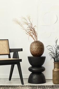 白いリビング ルームのインテリアのスタイリッシュな構成で、デザイン椅子、黒い木のスツール、花瓶にドライフラワー、カーペットの装飾、壁に絵画が飾られています。