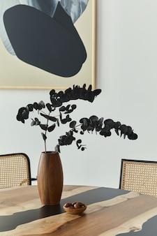 Стильная композиция на дизайнерском столе с элегантными черными цветами эвкалипта в деревянной вазе и орехами. интерьер современной столовой ..