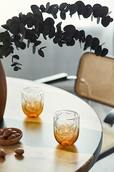 エレガントなグラス、ナッツ、木製の花瓶に黒いユーカリの花をあしらったデザインテーブルのスタイリッシュな構図。モダンなダイニングルームのインテリア。 Premium写真