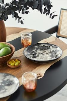 エレガントなプレート、グラス、フルーツ、木製の花瓶に黒いユーカリの花をあしらったデザインテーブルのスタイリッシュな構図。モダンなダイニングルームのインテリア。