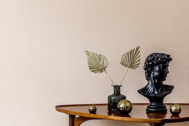 花瓶に金のボール、フィギュア、紙の花を備えたデザインの木製テーブルのスタイリッシュな構成。ベージュの背景の壁。リビングルームのミニマルなコンセプト。スペースをコピーします。テンプレート。