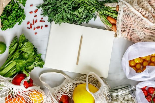 ノート、ゼロウェイストニュートラルバッグ、シード、卵、バイオ野菜、エコフルーツを備えた大理石のテーブルのスタイリッシュな構成