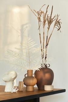 ドライフラワー、本、装飾が施されたデザインの花瓶を備えた木製のテーブルのスタイリッシュな構成。壁の美しい影。モダンなインテリアの抽象的なコンセプト。レンプレート。