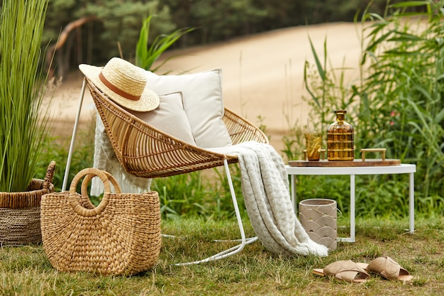 Stylish composition of outdoor garden on the lake with design rattan armchair coffee table plaid pillows drinks and elegant accessories