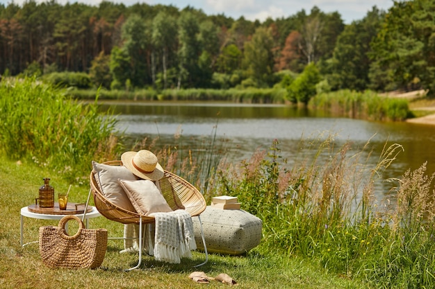 Stylish composition of outdoor garden on the lake with design rattan armchair, coffee table, plaid, pillows, drinks and elegant accessories.