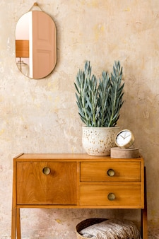 Stylish composition of retro living room interior with wooden vintage commode, gold pink mirror, plant, rattan basket, plaid, decoration and elegant personal accessories in wabi sabi home decor.